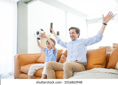 Portrait of happy boy watching soccer match with father on sofa at home