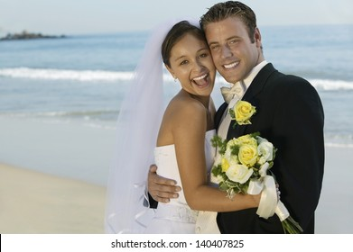Portrait of a happy bride and groom embracing on the beach