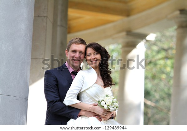Portrait of happy bride and groom near columns