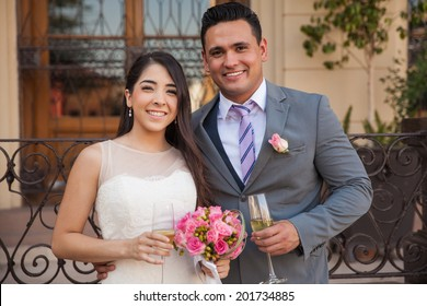Portrait of happy bride and groom toasting with champagne after getting married