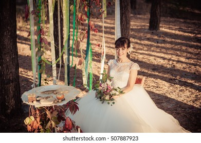 Portrait of the happy bride on wedding walk in the fall in the wood. Wedding in the autumn