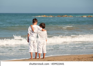 Portrait of happy brothers in white shirts on background of sea, outdoor, Spain