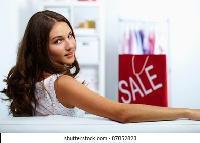 Portrait of happy brunette looking at camera with sale bag on background
