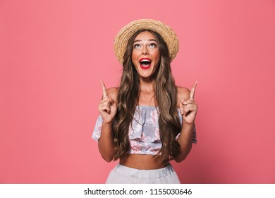 Portrait of happy brunette woman 20s wearing straw hat screaming and pointing fingers upward isolated over pink background in studio