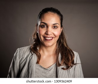 portrait of happy brunette woman smiling on a gray background