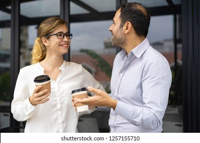 Portrait of happy business colleagues talking at coffee break. Young woman and mid adult bearded man standing outside with takeout coffee and having friendly conversation. Colleagues concept