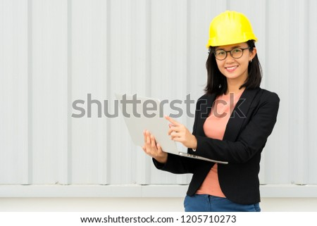 21d458d4f8d Portrait happy business engineer woman standing using laptop with yellow  safety helmet on metal sheet wall