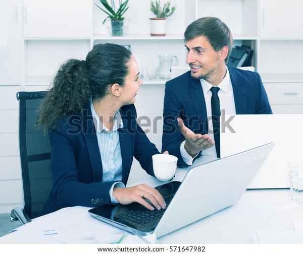 portrait of happy business man and woman colleagues chatting about work in office