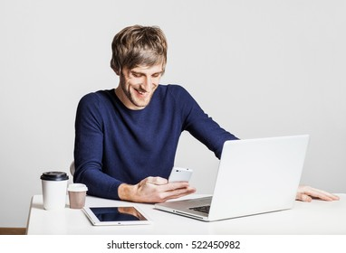 Portrait of a happy business man working with laptop computer and texting on his smartphone