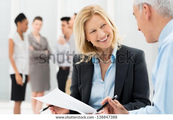 Portrait von glücklichen Geschäftsleuten, die im Büro miteinander diskutieren