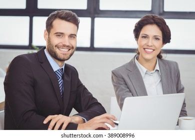 Portrait of happy business people with laptop at desk in office