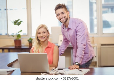 Portrait of happy business people looking at laptop in creative office