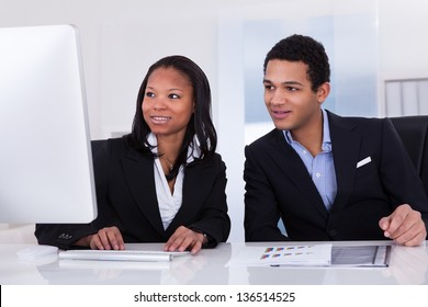 Portrait Of Happy Business People Sitting At The Desk