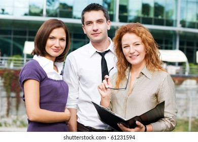 Portrait of happy business people staying outdoor and looking at the camera. People ready to cooperate with any business company.