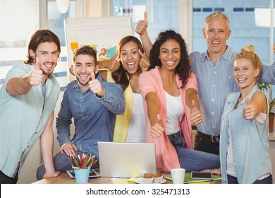 Portrait of happy business people with technologies showing thumbs up in creative office