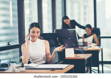 Portrait of a happy business woman sitting at her workplace in office - Shutterstock ID 1355131265
