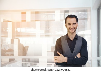 Portrait of happy businessman with arms crossed standing in office,