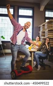 Portrait of happy businessman enjoying self-balanced board in creative office
