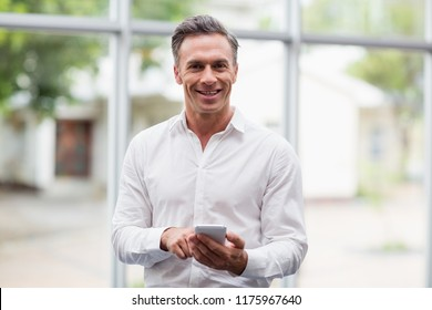 Portrait of a happy businessman holding mobile phone