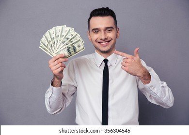 Portrait of a happy businessman holding money isolated on a white background