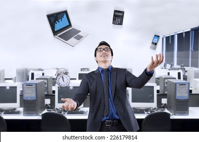 Portrait of happy businessman juggling with business items in the office