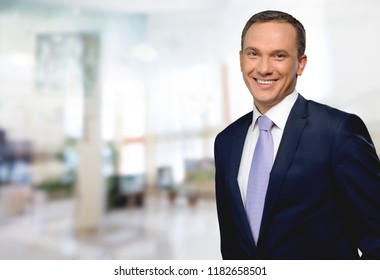 Portrait of happy businessman on background