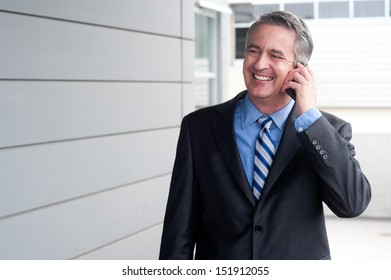 portrait of a happy businessman on the phone outside