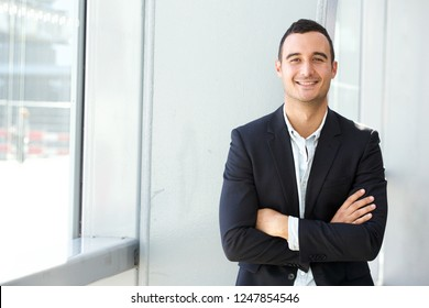 Portrait of happy businessman posing with arms crossed