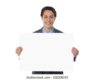 Portrait of a happy businessman showing an empty billboard against white background