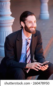 Portrait of a happy businessman sitting with mobile phone