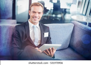 Portrait of happy businessman sitting on sofa and using digital tablet in office