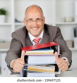 Portrait of happy businessman with stack of books gesturing thumbs up in office