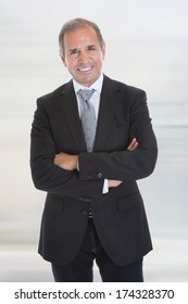 Portrait Of Happy Businessman Standing With Arm Crossed