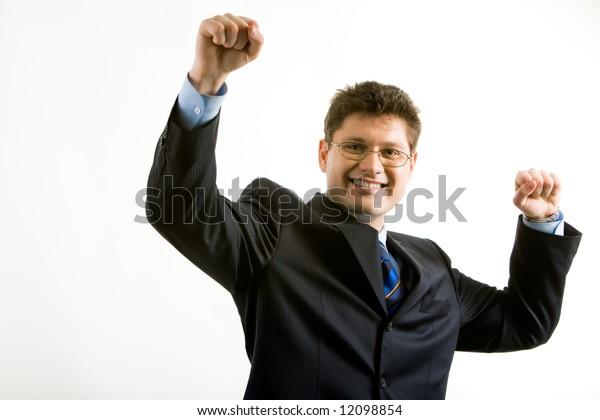 Portrait of happy businessman in suit raising his hands