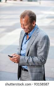 Portrait of happy businessman text messaging