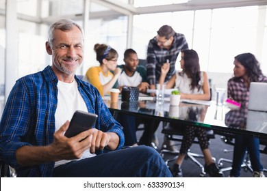 Portrait of happy businessman using mobile phone with team working in background at creative office