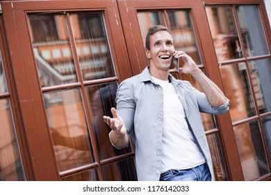 Portrait of a happy businessman walking outdoors with mobile phone. Man with phone. Happy surprised travaller talking phone using free internet connection. Businessman outdoor with phone.