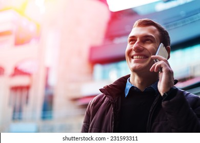 Portrait of a happy businessman walking outdoors with mobile phone. Man with phone. Happy man talking phone. Man walking with phone. Man outdoor with phone. Businessman outdoor with phone.