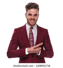 portrait of happy businessman wearing a grena colored suit rubbing his palms together and looking down to side while standing on white background