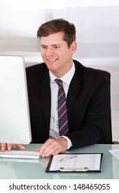 Portrait of happy businessman working at office