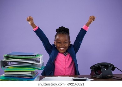 Portrait of happy businesswoman with arms raised by files and telephone while sitting at desk against purple wall in office