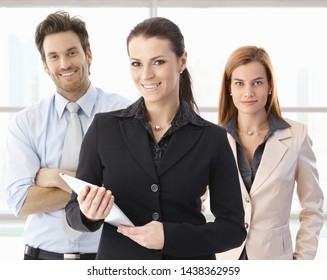 Portrait of happy businesswoman and business team looking at camera, smiling.