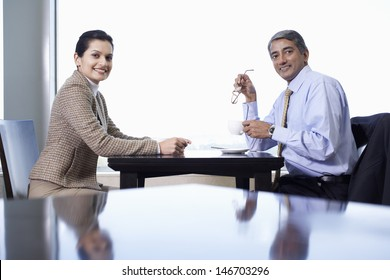 Portrait of happy businesswoman and businessman at cafe table