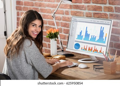 Portrait Of A Happy Businesswoman With A Graph On Computer Screen