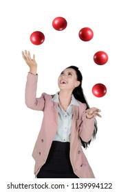 Portrait of happy businesswoman is juggling with red balls while standing in the studio, isolated on white background