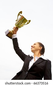 Portrait of happy businesswoman raising championship cup