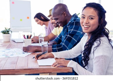 Portrait of happy businesswoman sitting with colleagues in conference room