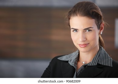 Portrait of happy businesswoman smiling in passageway.?