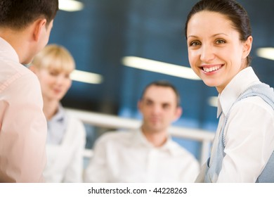 Portrait of happy businesswoman smiling at camera on background of working employees