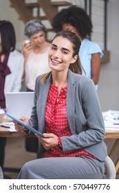 Portrait of happy businesswoman using digital tablet In office